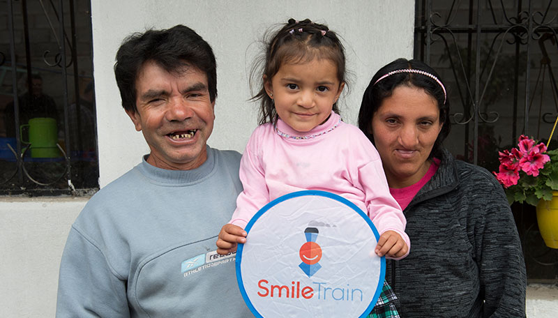 Estefania with mom and dad holding a Smile Train sign